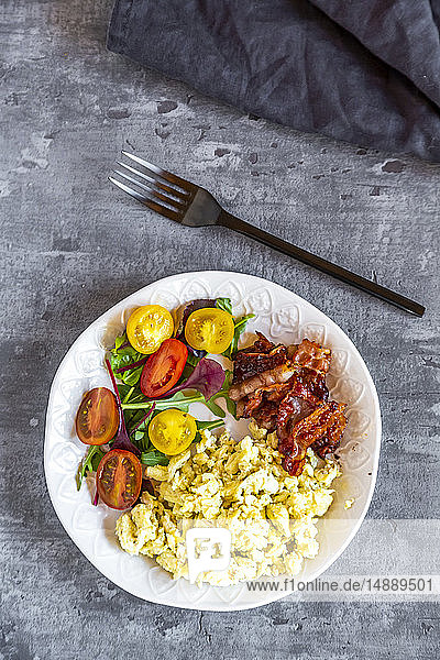 Scrambled eggs with fried bacon and salad with tomato  low carb  from above