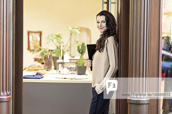 Eine reife Frau steht in der Tür eines Modegeschäfts und hält ein digitales Tablett