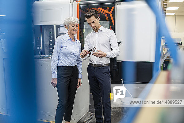 Businessman and senior businesswoman measuring workpiece in a factory