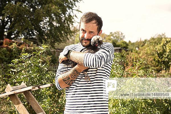 Porträt eines Mannes  der mit polnischen Hühnern im Garten kuschelt