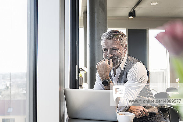 Smiling mature businessman with laptop at the window