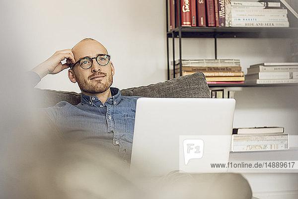 Mann sitzt auf Couch  benutzt Laptop