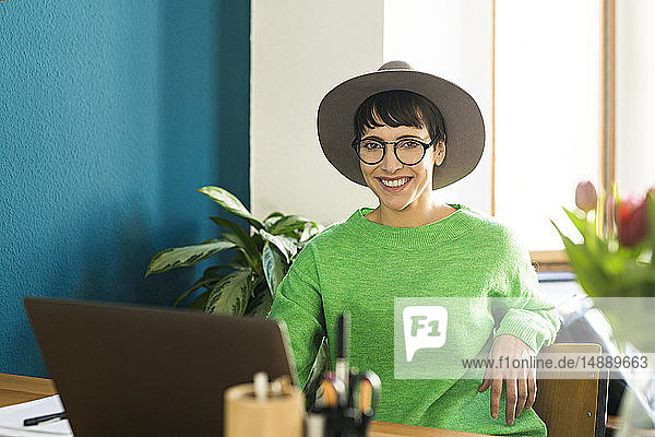 Portrait of happy businesswoman in home office working at her laptop