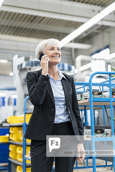 Smiling senior businesswoman on cell phone in a factory