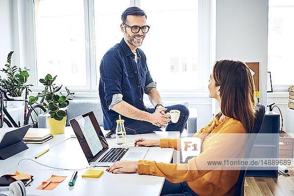 Zwei Kollegen sprechen am Schreibtisch im Büro