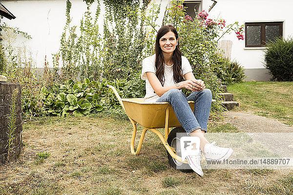 Porträt einer lächelnden Frau  die in einer Schubkarre im Garten sitzt