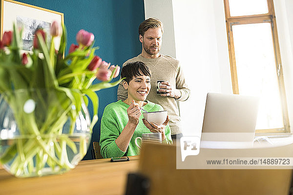 Happy couple lookig at laptop in home office