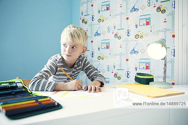 Junge macht Hausaufgaben am Schreibtisch im Kinderzimmer