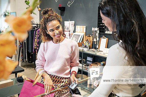 Young customer paying contactless in a fashion store