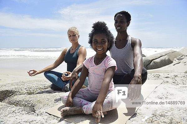 Mutter mit Tochter und Freundin bei einer Yoga-Übung am Strand