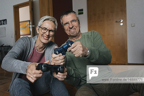 Happy senior couple playing video game at home