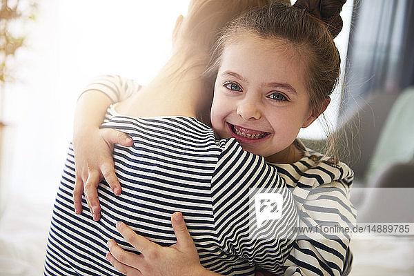 Glückliche Tochter umarmt Mutter