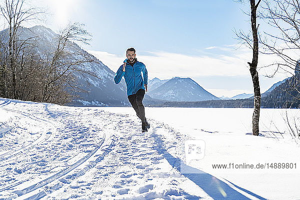 Deutschland  Bayern  sportlicher Mann rennt im Winter durch Schnee