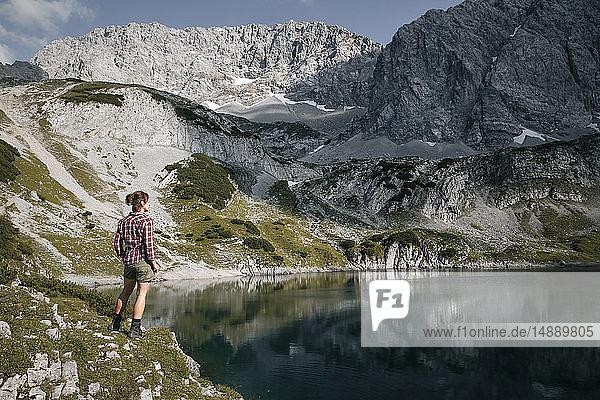 Austria  Tyrol  woman standing at lake Drachensee looking at view