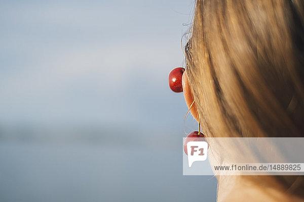 Rückenansicht einer jungen Frau  die Kirschen am Ohr trägt  Nahaufnahme