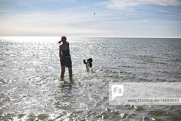 Frankreich  Rückenansicht einer Frau  die für ihren Hund einen Ball ins Meer wirft