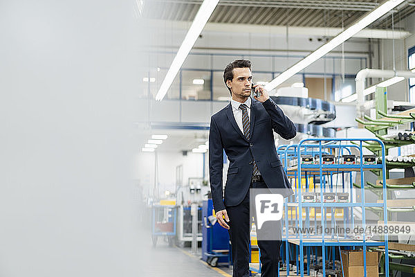 Businessman on cell phone in a factory