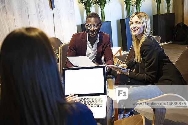 Geschäftsleute sitzen in einer Hotellobby und arbeiten zusammen