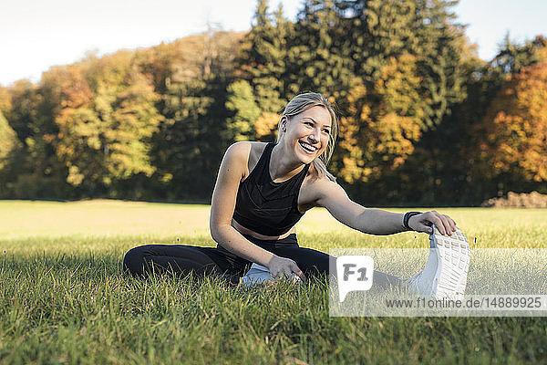 Junge Frau streckt ihr Bein auf einer Wiese