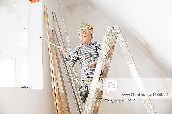 Junge mit Taschenregel auf Leiter auf dem Dachboden  der renoviert werden soll