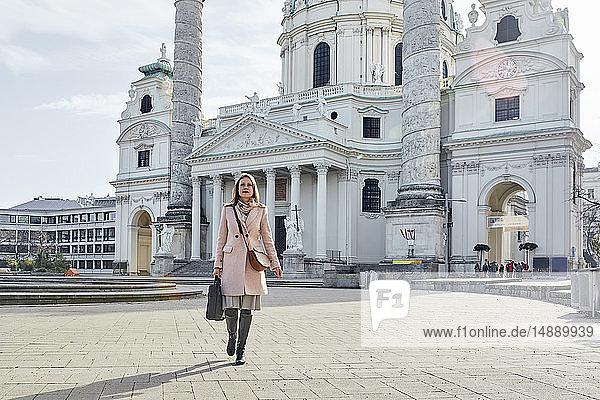 Österreich  Wien  junge Geschäftsfrau mit Laptoptasche beim Überqueren des Karlsplatzes