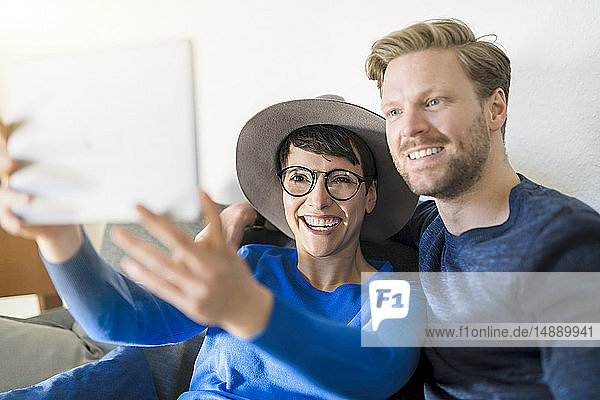 Happy casual couple taking a selfie with tablet in living room