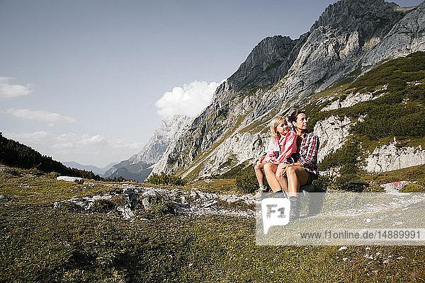 Österreich  Tirol  Mutter mit Tochter in Berglandschaft ruhend