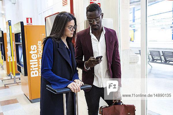 Geschäftsleute überprüfen Smartphone am Bahnhof
