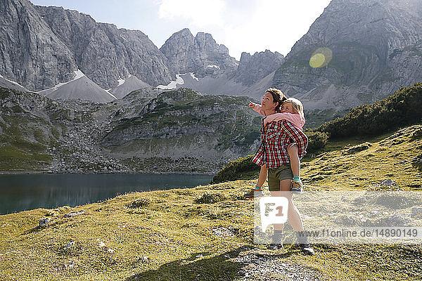 Österreich  Tirol  Mutter trägt Tochter huckepack am Drachensee