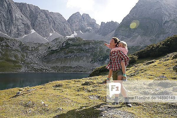 Austria  Tyrol  mother carrying daughter piggyback at lake Drachensee
