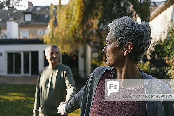 Liebenswertes älteres Ehepaar hält im Garten Händchen