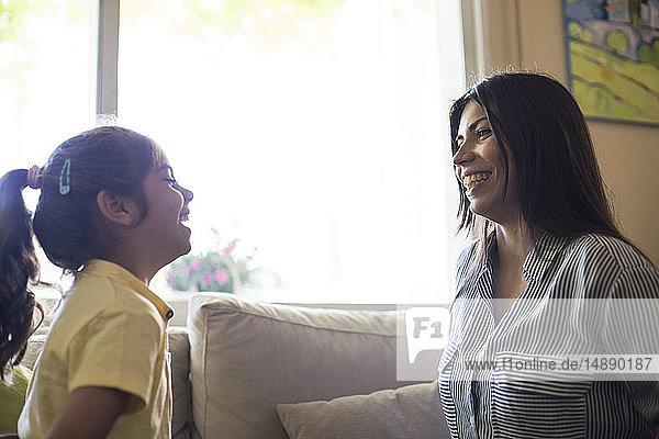 Glückliche Mutter und Tochter zu Hause auf der Couch einander gegenüber