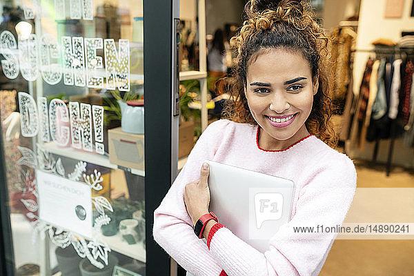 Junge Frau steht in der Tür eines Modegeschäfts und hält einen Laptop