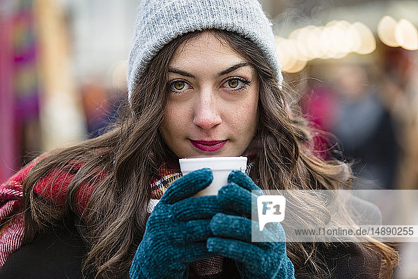 Portrait of beautiful young woman holding hot drink at Christmas market