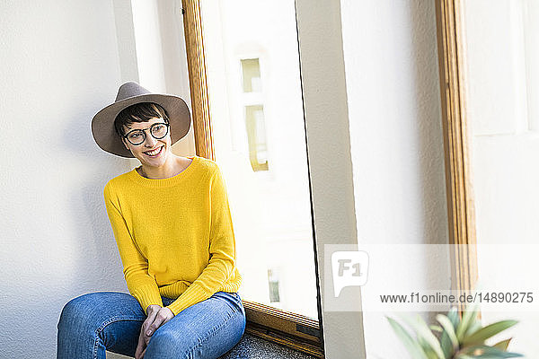 Happy woman sitting on windowsill looking outside