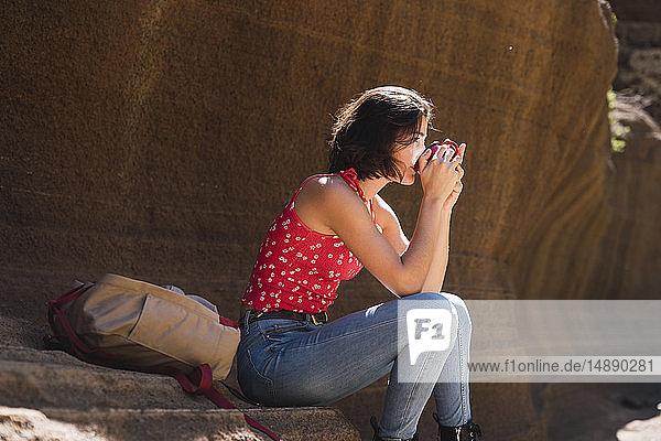 Spain  Gran Canaria  Barranco de las Vacas  young woman having a rest drinking water