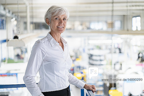Portrait of confident senior businesswoman on upper floor in factory