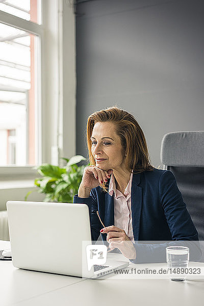 Businesswoman sitting in office  working on laptop