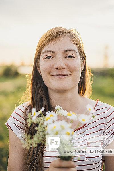 Porträt einer lächelnden jungen Frau mit einem Strauss gepflückter Wildblumen