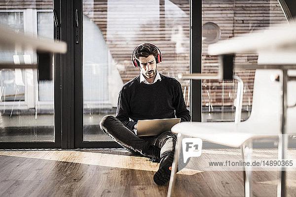 Geschäftsmann sitzt auf dem Boden seines Büros und benutzt Laptop und Kopfhörer