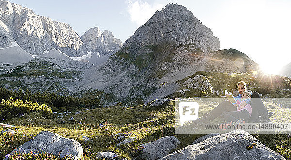 Austria  Tyrol  mother and daughter reading book in mountainscape at sunset
