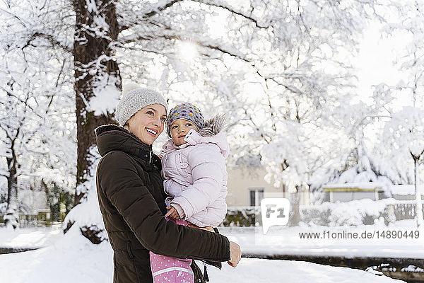 Glückliche Mutter trägt Tochter in Winterlandschaft