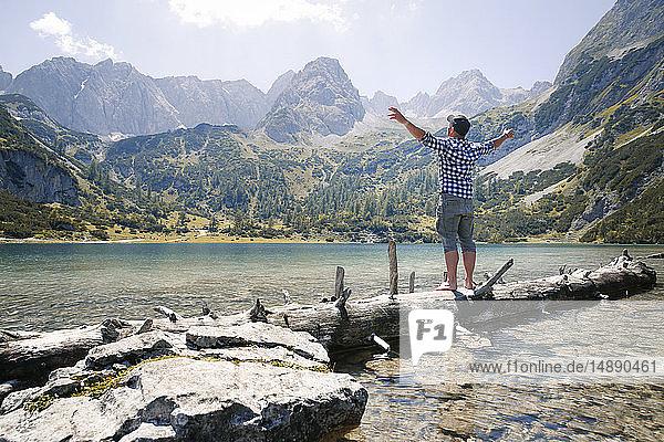 Austria  Tyrol  man standing on tree trunk at lake Seebensee
