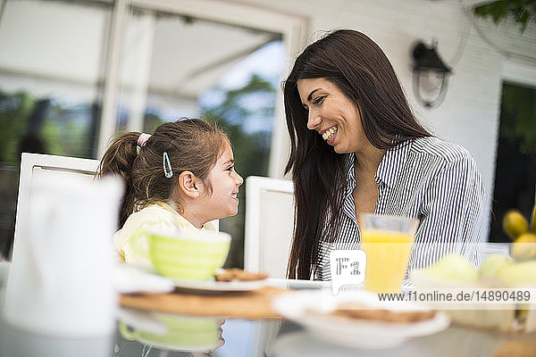 Happy mother and daughter having breakfast at home