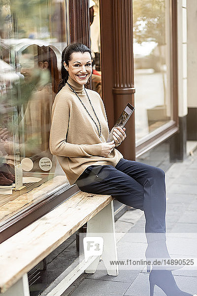Mature woman sitting in front of her fashion store  using tablet