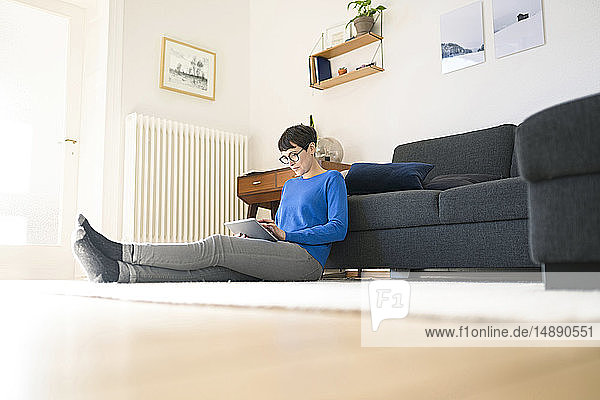Casual short-haired woman relaxing in modern living room using a tablet