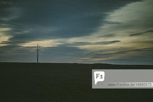 Deutschland  Sylt  Wiese im Abendlicht  Wolken  Tristesse  Strommast