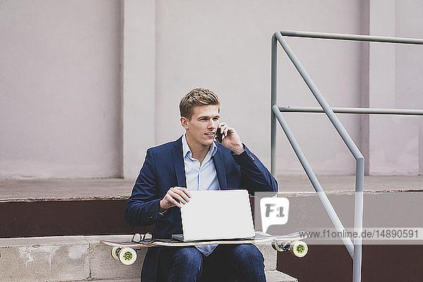 Junger Geschäftsmann mit Skateboard und Laptop sitzt draußen auf der Treppe und telefoniert mit dem Handy