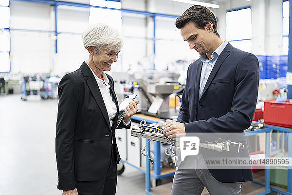 Smiling businessman and senior businesswoman examining workpiece in a factory