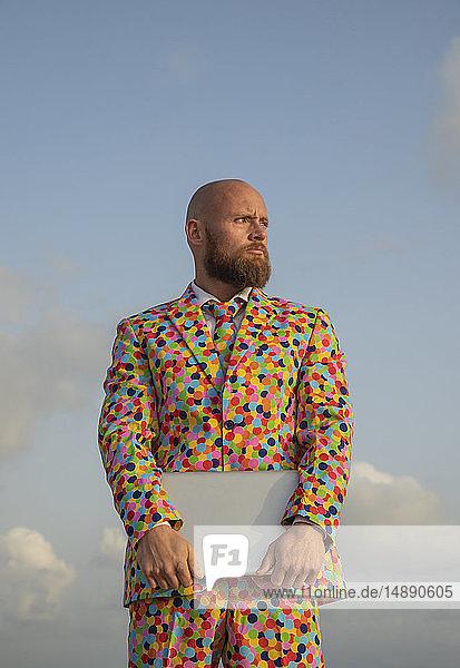 Porträt eines kahlköpfigen Mannes mit Bart im Anzug mit bunten Polka-Punkten  der einen Laptop hält